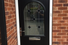 Composite door with decorative glass
