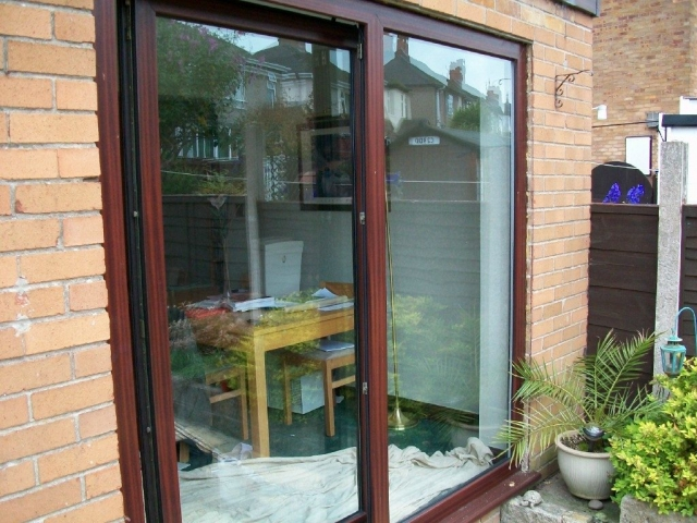 dark wood effect patio windows being fitted by the Window Repair Centre