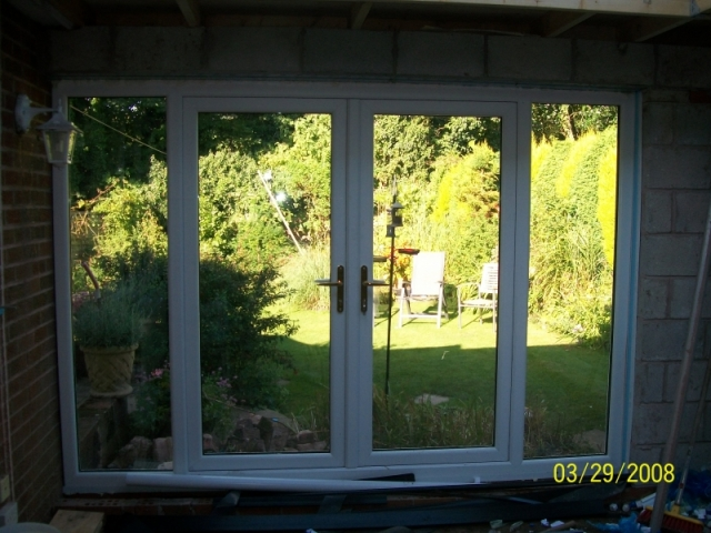 internal view of new upvc french doors and windows being fitted in an extension