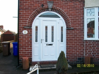 White upvc front door and side panels used in a porch infill