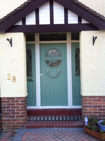Modern composite door in chartwell green with circular window and decorative glass. Matching side panels.