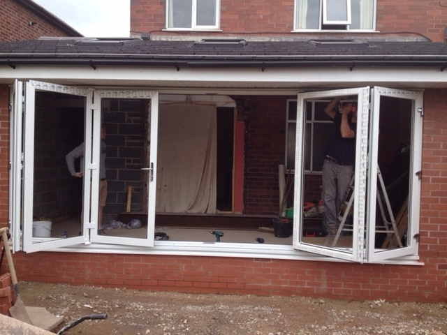 Bifold windows being fitted in an extension