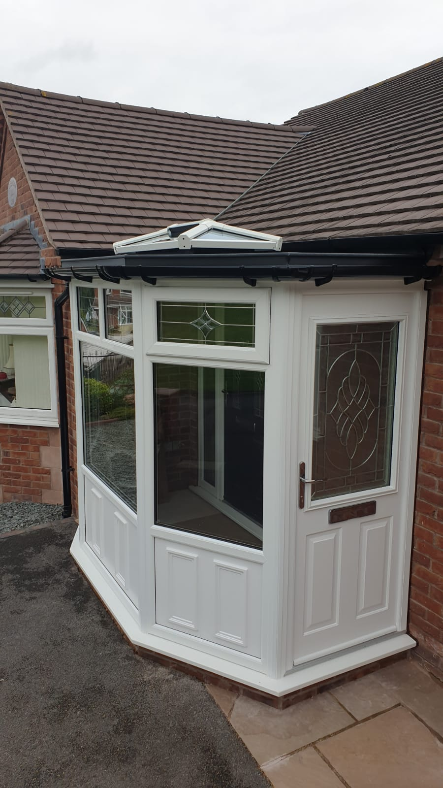 Photo of a door with a porch showing a lantern style roof