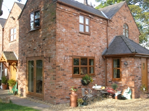 timber effect windows with light oak fascias and  guttering